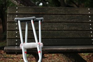 pair of crutches leaning against a park bench | Colorado Springs Bad Faith Attorney