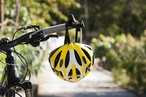 Yellow Helmet Hanging From A Bicycle