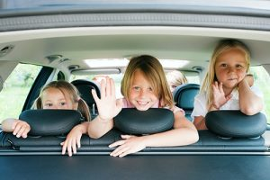 kids in backseat of car facing the back and waving | Seat Belts and Car Seats Really Do Save Lives