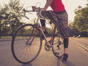 A young woman wearing a skirt is riding a bicycle in the park at sunset | Bicycle Accident Injuries