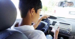 young woman checking phone behind wheel | How Can You Help End the Distracted Driving Epidemic?