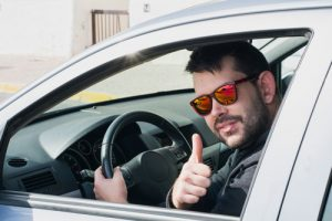 lame-guy-in-sunglasses-behind-wheel-giving-a-stupid-thumbs-up-to-camera-sm-300x200