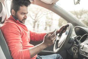 young indian man texting behind wheel | study on Distracted Driving Behavior