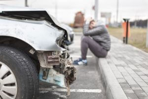 car-with-smashed-front-end-upset-driver-head-in-hands-sm-300x200