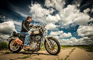 man-sitting-on-motorcycle-looking-down-road-sm-300x193