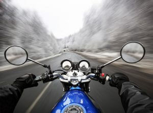 speeding-blue-motorcycle-on-road-in-snowy-woods-from-driver-perspective-sm-300x223