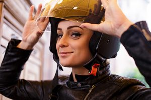 young-woman-adjusting-motorcycle-helmet-looking-at-camera-sm-300x200