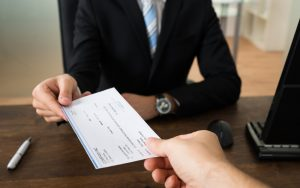 Attorney Handing A Client A Check From A Personal Injury Settlement In Colorado