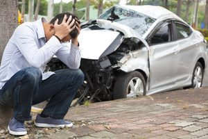 Distrought Man Next To A Totaled Car