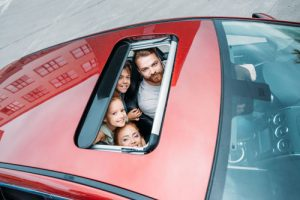 Family Looking Through The Sunroof Of Their Car