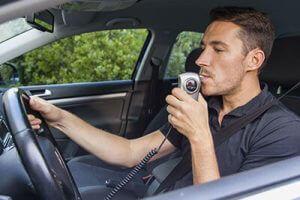 Man Using A Breathalyzer In His Car