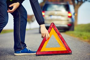Person Putting A Warning Sign In The Road